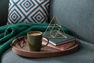 Stylish tray with different interior elements and coffee on sofa