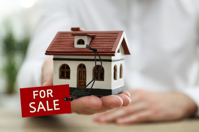 Real estate agent holding house model with SALE label indoors, closeup