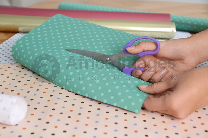 Woman cutting fabric with scissors at table, closeup
