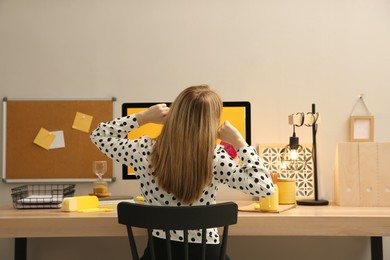 Woman sitting at wooden desk with computer near light wall, back view. Interior design