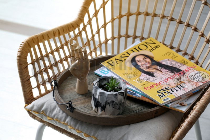 Wooden tray with houseplant and magazines on chair indoors