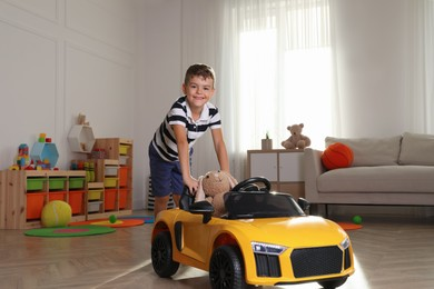 Cute little boy playing with big toy car and stuffed bunny at home