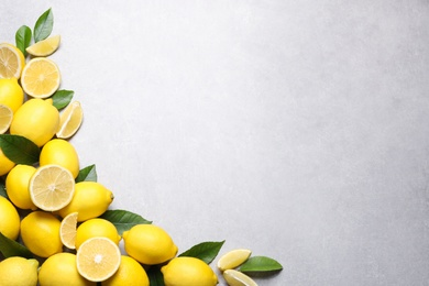 Many fresh ripe lemons with green leaves on light grey table, flat lay. Space for text