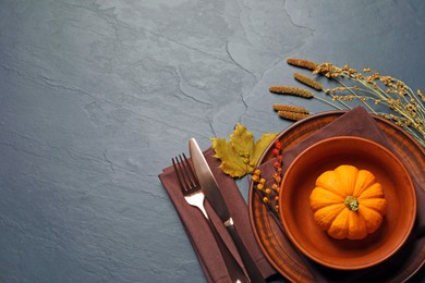 Autumn table setting with floral decor and pumpkin on dark grey background, flat lay. Space for text