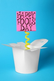 Lunch box with Happy Fools' Day note on light blue background