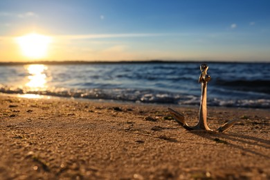 Metal anchor on shore near river at sunset