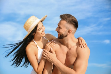 Happy young couple in beachwear on sunny day