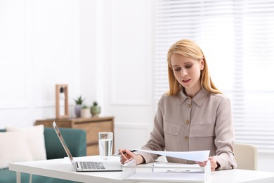 Professional lawyer working on laptop at table in office