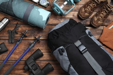Flat lay composition with backpack and other different camping equipment for tourism on wooden background