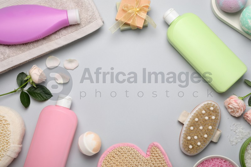Flat lay composition with shower gel bottles and roses on light grey background, space for text
