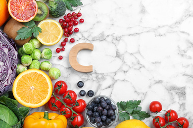 Different products rich in vitamins and letter C on white marble table, flat lay. Space for text