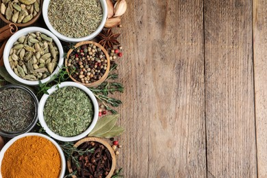 Flat lay composition with different natural spices and herbs on wooden table, space for text