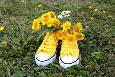 Shoes with beautiful yellow flowers on grass outdoors