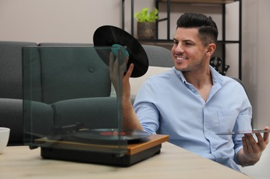 Happy man choosing vinyl record to play with turntable at home