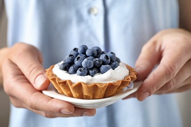 Woman holding plate with blueberry tart, closeup. Delicious pastries