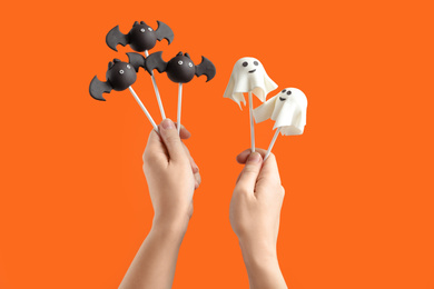 Woman with delicious ghost and bat shaped cake pops on orange background, closeup. Halloween celebration