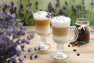 Delicious latte with lavender and coffee beans on wooden table