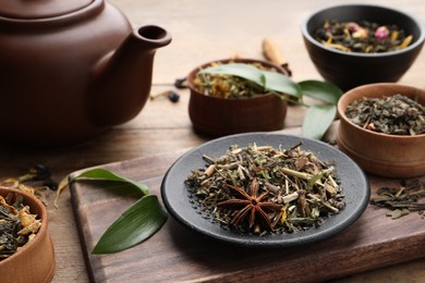 Different dry aromatic teas on wooden table