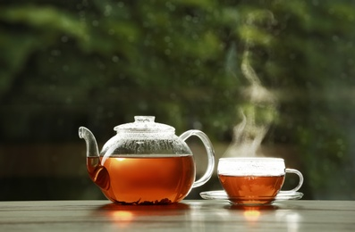 Teapot and cup of hot tea on wooden table against blurred background, space for text