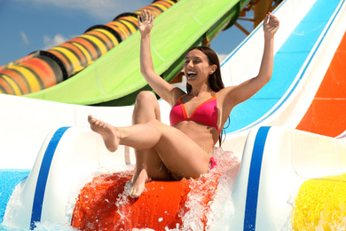 Young woman on slide at water park. Summer vacation