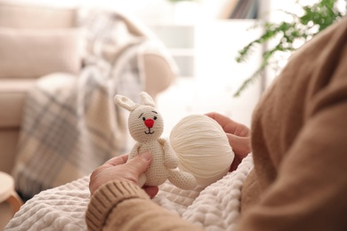 Elderly woman with knitted bunny at home, closeup. Creative hobby