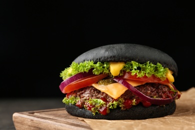 Board with black burger on table, closeup