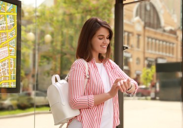 Young woman checking time while waiting for public transport at bus stop