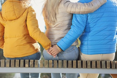 Man holding hands with another woman behind his girlfriend's back on bench in park, closeup. Love triangle