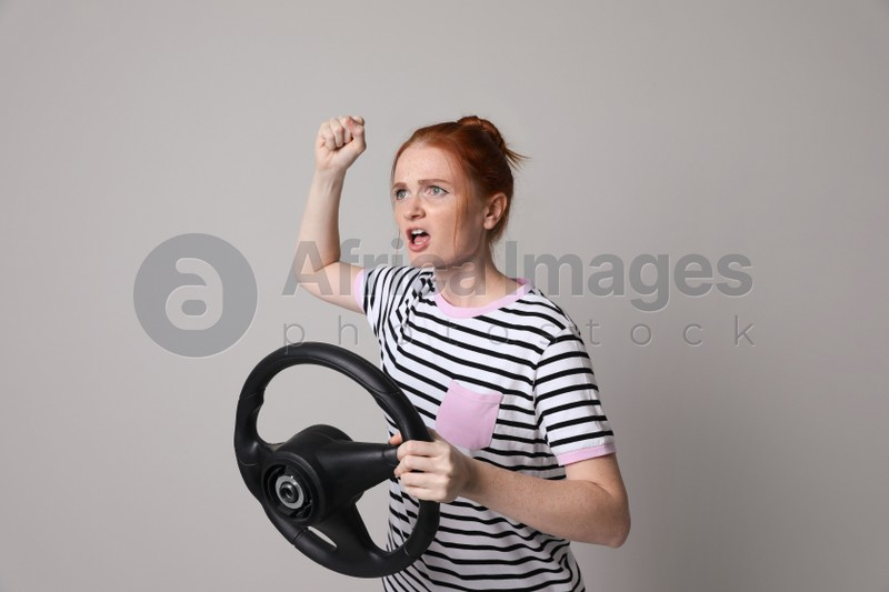 Emotional young woman with steering wheel on grey background