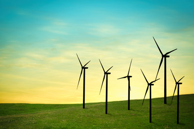 Silhouettes of wind turbines at sunset. Alternative energy source