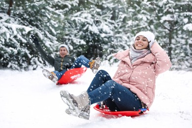 Happy couple sledding outdoors on winter day. Christmas vacation