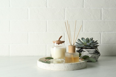 Candles, eucalyptus branches and aromatic reed air freshener on white table near brick wall, space for text. Interior elements
