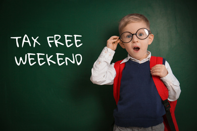 Little boy with backpack and text TAX FREE WEEKEND written on chalkboard