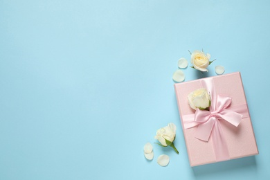 Pink gift box and beautiful flowers on light blue background, flat lay. Space for text