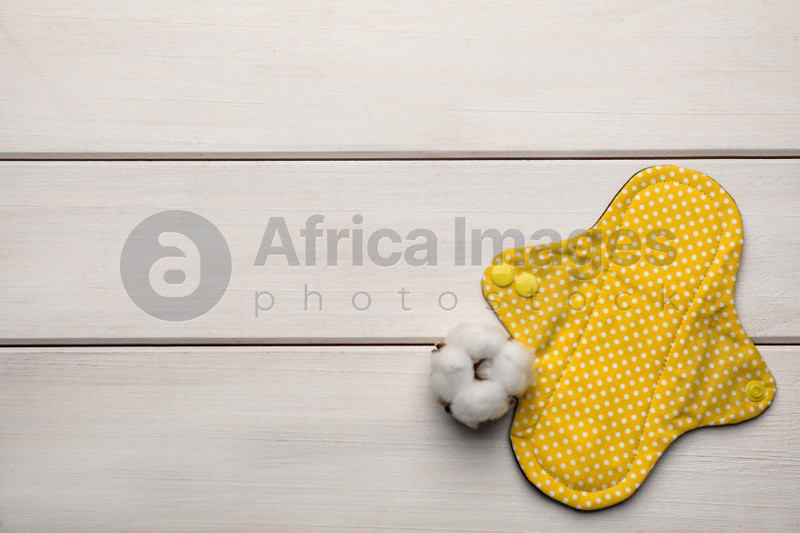 Reusable cloth menstrual pad and cotton flower on white wooden table, flat lay. Space for text