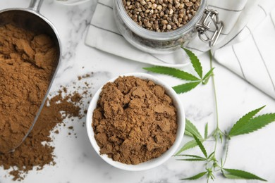 Hemp protein powder, seeds and fresh leaves on white marble table, flat lay
