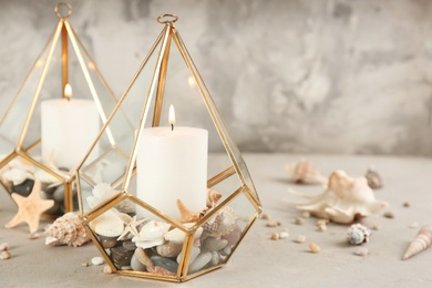Stylish glass holders with burning candles, seashells and pebbles on light stone table