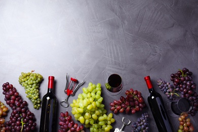 Flat lay composition with fresh ripe juicy grapes and wine on grey table, space for text