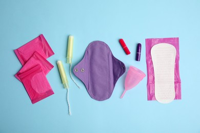 Tampons and other menstrual hygienic products on light blue background, flat lay