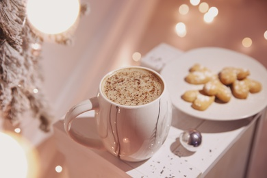 Cup of tasty hot drink and cookies indoors. Christmas atmosphere