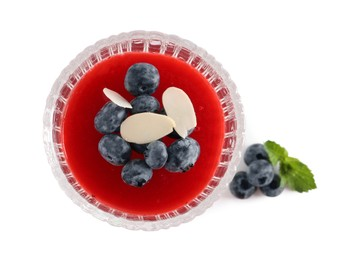 Delicious fruit jelly with fresh blueberries and almond flakes on white background, top view