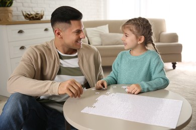 Happy father and his daughter playing with puzzles at home