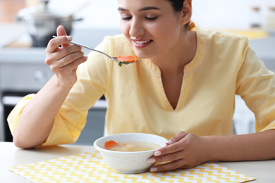 Young woman eating tasty vegetable soup at table in kitchen