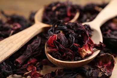 Wooden spoon with dry hibiscus tea on table, closeup