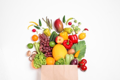 Paper bag with assortment of fresh organic fruits and vegetables on white background, top view