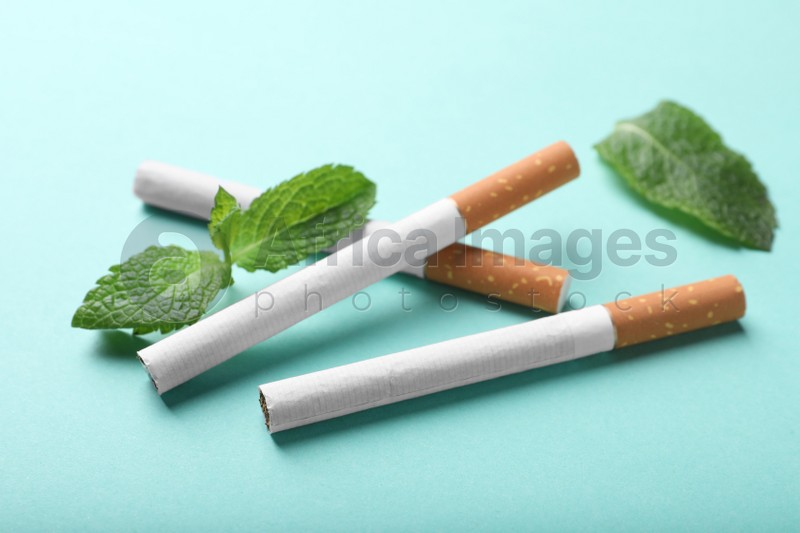 Menthol cigarettes and mint on turquoise background