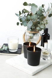 Burning aromatic candles and perfume on table, space for text