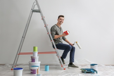 Male decorator sitting on ladder in empty room