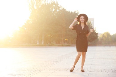 Beautiful young woman in stylish black dress and hat with cup of coffee on city street
