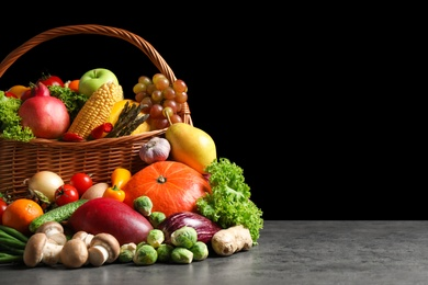 Assortment of fresh organic fruits and vegetables on grey table. Space for text